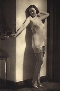 Model in wearing silky corset, with girdle.     Date: 1935