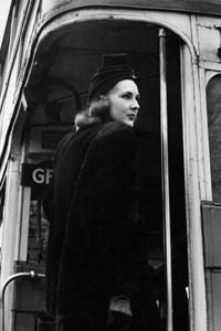 A woman in a stylish coat and turban style hat climbing aboard the no. 7 Routemaster London bus which is destined for Holborn by the looks of things.     Date: 1940s