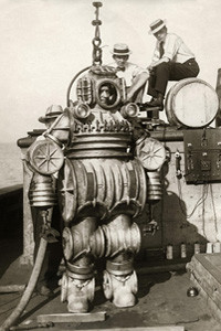 Diver in metal diving suit attached to cable