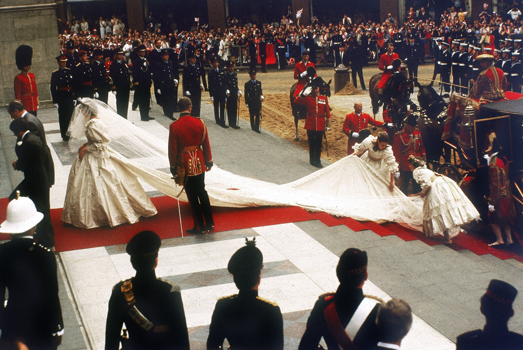 A photograph of Lady Diana Spencer arriving at St Paul's Cathedral in the City of London for her marriage to Prince Charles, Prince of Wales. Her dress and train, designed by David and Elizabeth Emmanuel is being arranged by her bridesmaids. Crowds of 60000 people lined the streets of London to watch the ceremony on 29th July 1981. Date: 29th July 1981