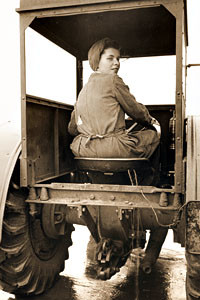 A Land Girl driving a tractor on a farm during World War II