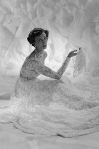 A frothy confection of lace  designed by Victor Stiebel  (1907-1976).  Dress has the  typical fitted bodice of the  fifties and billowing skirt.  Model holds lace handkerchief.     Date: 1950s