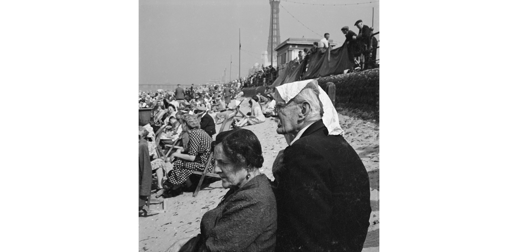 Holiday makers on an crowded beach with an elderly couple in the foreground and Blackpool Tower visible in the distance Date: 1946 - 1955