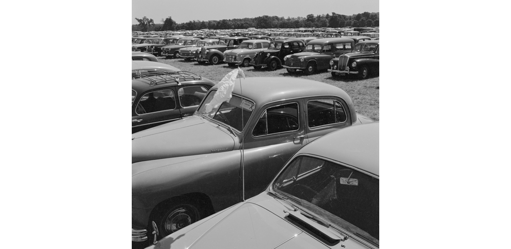 A view across the car-parking field at the Royal Show, Oxford, with a car flying a handkerchief from its radio aerial in the foreground Date: Jul 1959