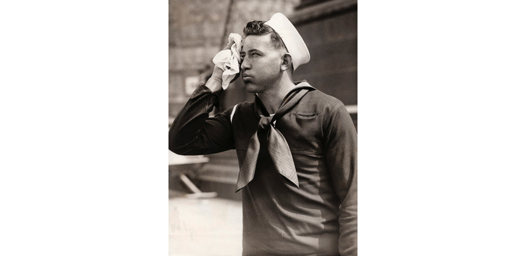A young sailor on a hot day in London, wiping his face with a handkerchief. Date: 15 June 1934