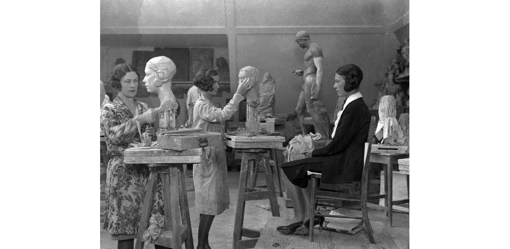 A class of female students at the London County School of Sculpture modelling clay busts based on live models. Date: 1930s