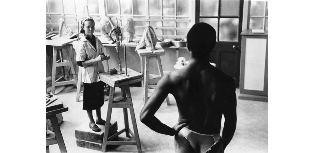 A sculpture student works on a clay model on a tripod, while a nude model poses for her, at the Central School of Art and Design (now Central St Martins College of Art and Design), London. Date: 1957