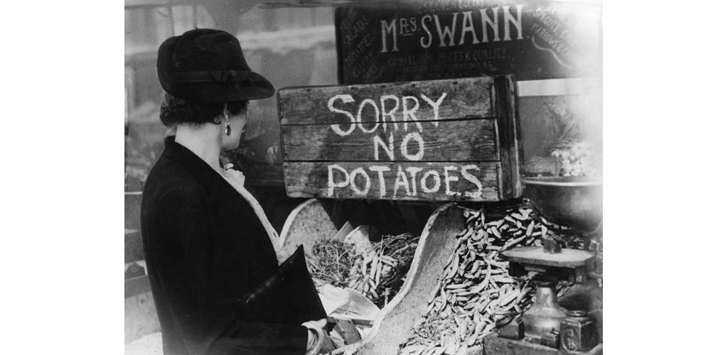 'Sorry No Potatoes' - a British housewife has limited choice for her vegetable purchasing, as potato stocks dry up due to tight rationing control over supply - December, 1941.     Date: 1941