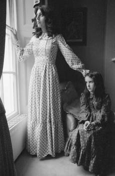 Fashion -- a woman and a girl, both wearing full-length Laura Ashley style dresses in floral fabric, looking out of a window. Date: circa 1970s