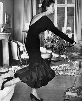 A short sheath dress in black French silk jersey with a deep V back and d飯llet鬠and a swirling hem of black taffeta, designed by Neil (Bunny) Roger, in whose house the photograph was taken, at Fortnum and Mason. Date: 1956