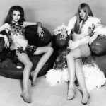 Two barefoot 'dolly birds' languidly reclining on  inflatable armchairs, wearing Space Age see-through  dresses.      Date: late 1960s