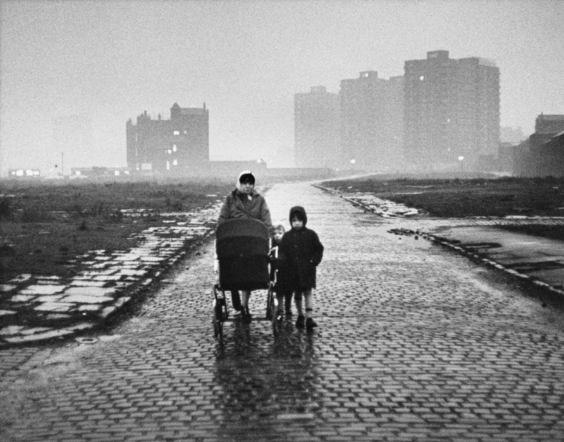 A scene of bleak desolation at Salford, Manchester, as a lone housewife pushing a pram, accompanied by her two young children walk along a cobbled street, cleared of the terraced houses which once lined it on either side. In the distance through the wet gloom and evening mist can be seen the new home for these cleared communities in high rise tower block flats. Photograph by Shirley Baker     Date: 1964