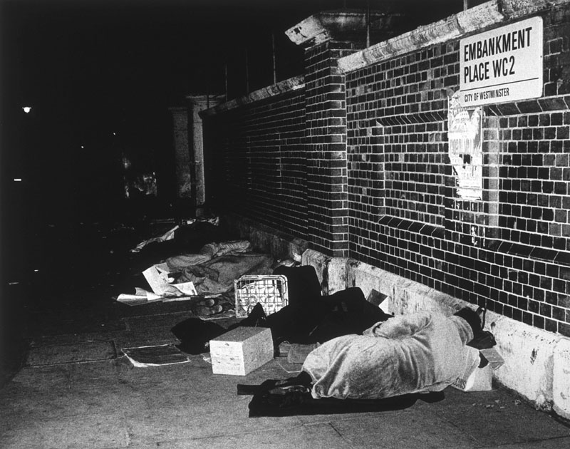 Homeless people sleeping in Embankment Place, central London, in a former 'dormitory' area.  They are disturbed at 4am by  street cleaning carts and are dispersed earlier during the tourist season.      Date: 1970s