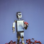 Futuristic silver robot toy walking in flowers.   1980s