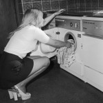 A young housewife loading up  her Miele washing machine  (with matching dishwasher) in her mini skirt and platform shoes.   1970s