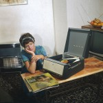 A dreamy teenager listening to  her new Astrud Gilberto LP on  her record player.     1960s