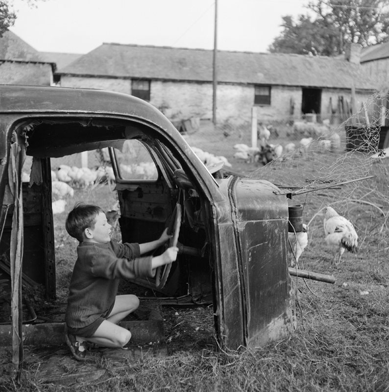 A young boy plays in the shell of an old car in a farmyard     Date: 01 Jan 1955 - 30 Apr 1957
