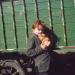 A young gypsy boy with bright red hair clutches his pet guinea pig close to his chest at an encampment in Surrey.   1973