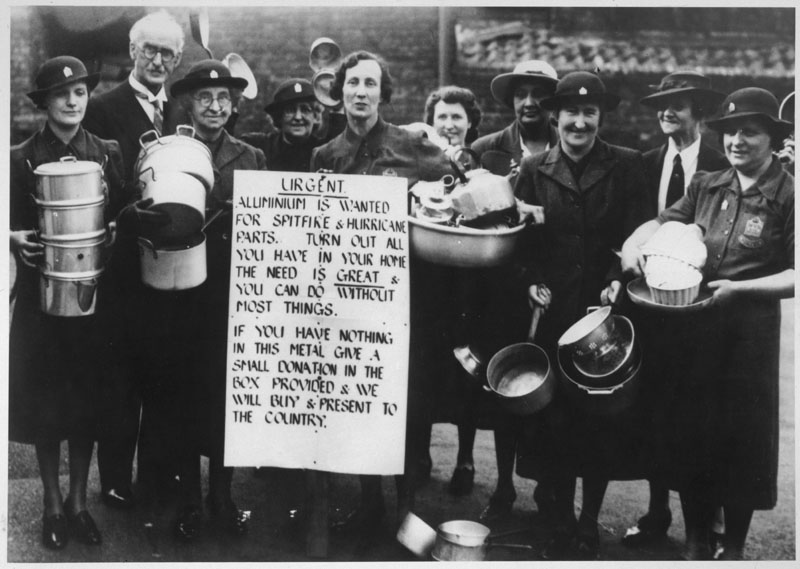 Cheery women of the WVS urge  the populace to donate their  aliminium pots and pans to provide parts for Spitfires and Hurricanes. Monetary gifts also acceptable.   July 1940