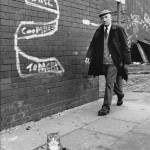 "A pretty cat stands proudly on the pavement in Salford, Manchester below a slogan which reads: ""Karl Coombe Tomcat"". A smartly-dressed elderly man wearing a flat cap strides purposely along behind. Photograph by Shirley Baker     Date: 1981"