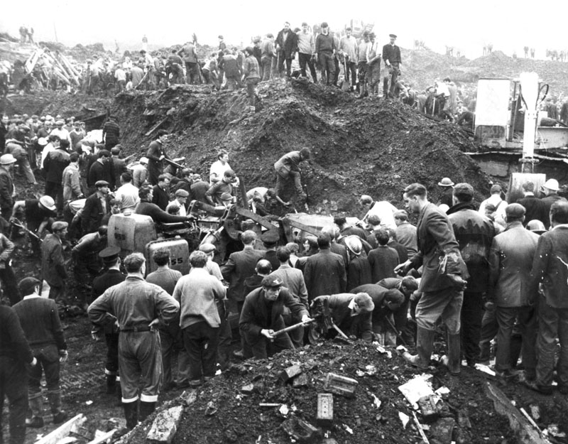Local people, including miners from nearby collieries, lead the effort to clear the debris following the landslide which saw a huge mass of excavated mining debris smash into the Welsh village of Aberfan. A farm, terraced houses and local schools were hit, and the tragedy cost the lives of 116 children and 28 adults.     Date: 21 October 1966