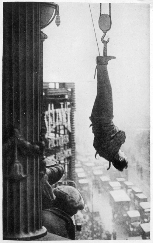 Harry Houdini (1874-1926), American stunt performer.  Suspended from the cornice of a New York skyscraper, he must somehow free himself of his chains and make his way to safety ... will he do it ? Is this one trick too many?   circa 1920s