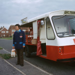 Fresh milk is delivered by the milkman, who stands by his milk  float.        Date: 1975