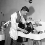 Man dressed In shirt, tie, waistcoat and apron, bent over a kitchen sink full of dirty dishes, cleaning a frying pan.    1930s