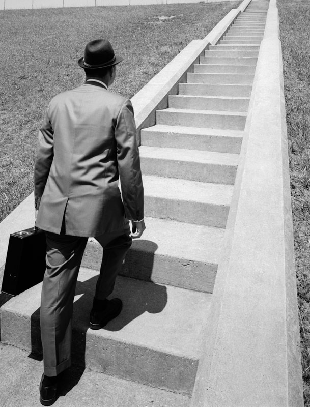 Businessman in suit and fedora carrying a briefcase, walking up a long flight of cement stairs.   circa 1960s