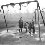 A group of children in a playground on a wet day, wondering how to get the swings untangled!    early 1930s