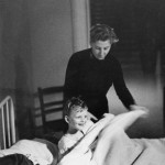 A little boy being put to bed with the help of staff at the Strawberry Fields orphanage in Liverpool.    circa 1950