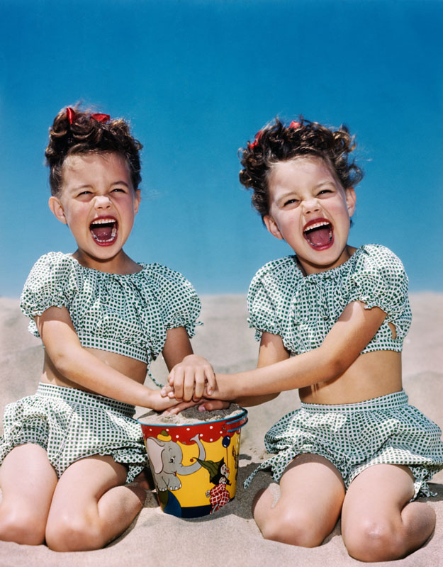 1940s 1950s SMILING LAUGHING TWIN GIRLS WEARING CHECKERED TWO PIECE BATHING SUITS PLAYING ON SANDY BEACH