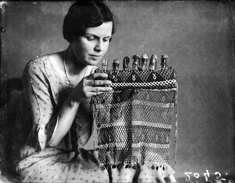 A young woman creating a tear bottle display, a mourning custom dating from Ancient Rome and Egypt, when mourners would bottle their tears for  burial with their loved ones.  early 1930s