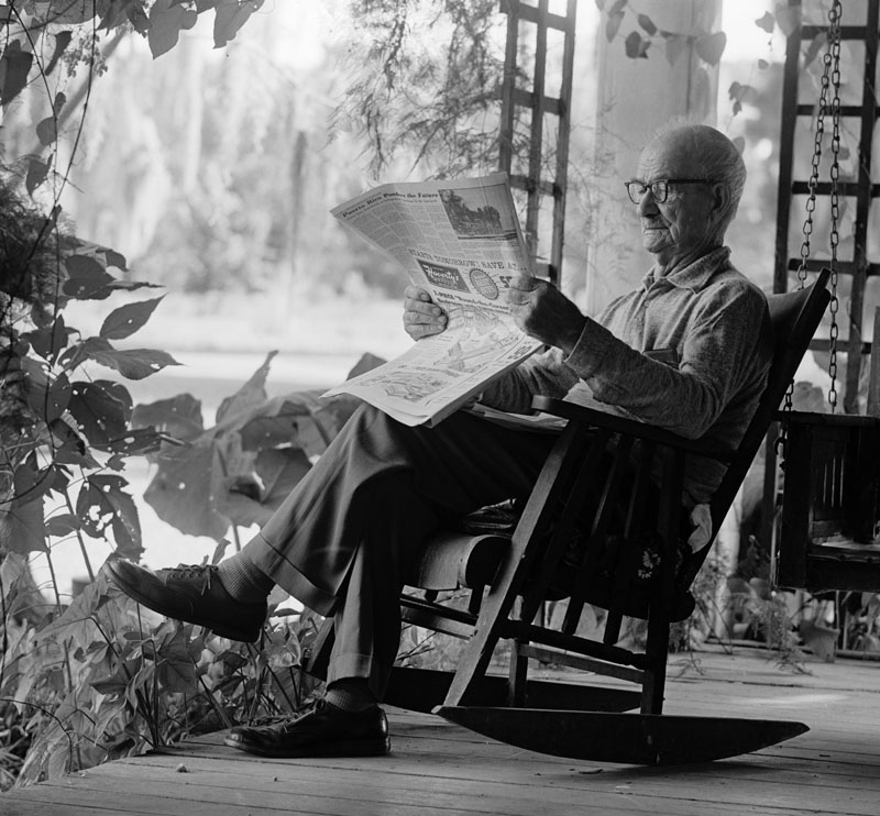 Elderly man In rocking chair reading newspaper on a porch.   1970s
