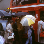 London Street Scene -- people with umbrellas crowding to get onto a number 11 bus on a rainy day.   1960s