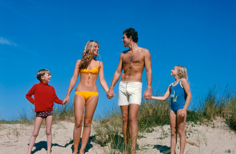 A family of four -- mother, father and two children -- holding hands on the sand dunes on a beach in Cornwall.      Date: 1970