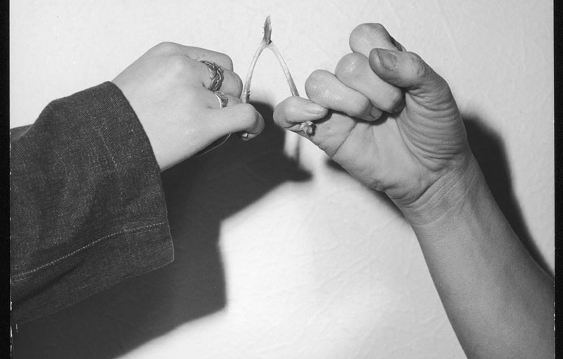 Pulling a wishbone to see who will come away with the larger part and the corresponding wish.     1970s