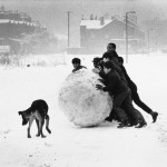 A group of black and Asian boys make a massive snowball on a wintry Manchester day. Photograph by Shirley Baker     Date: 1968