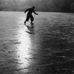 A solitary ice skater making patterns on the ice of a frozen river.    1950s