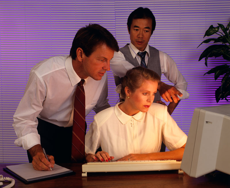 1990s business people working together at desktop computer     Date: 1990s