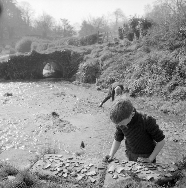 Two boys search for broken pottery in a muddy sheepwash on Winkle Street in Calbourne, Isle of Wight. Dating to probably the 17th century, the sheepwash is an enclosure of Bembridge stone walls about 3 feet in height. A rare survival.     Date: 1960s