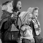 1950s FOUR CHILDREN TWO BOYS TWO GIRLS SINGING CHRISTMAS CAROL TOGETHER HOLDING CANDLE LANTERN