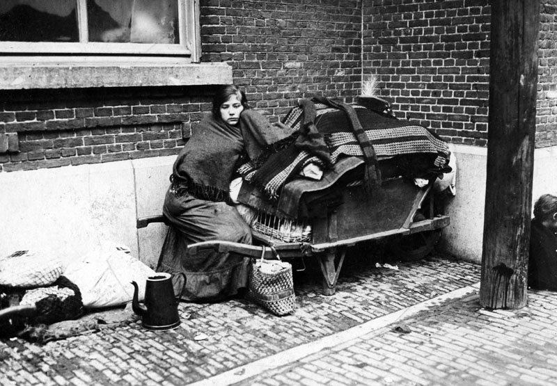 A Belgian refugee girl during the First World War, who sits in a street corner, guarding her goods., 01.11.1914-30.11.1914