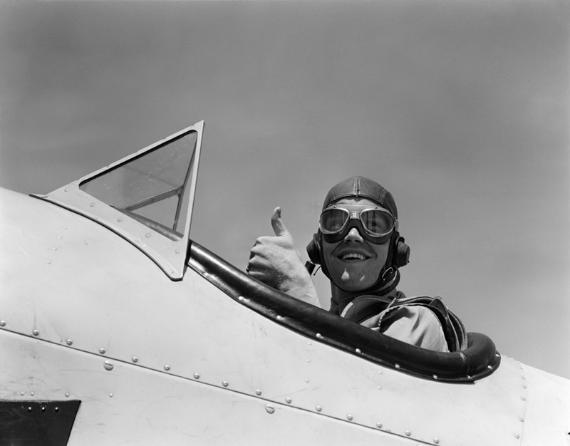 Smiling Army Air Corps pilot in open cockpit in a leather flying helmet giving a thumbs-up sign.   1940s