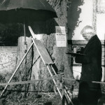 STANLEY SPENCER (1891-1959), English artist, photographed in profile whilst at work on his painting of Cookham Churchyard, Berkshire, England.      Date: 1958