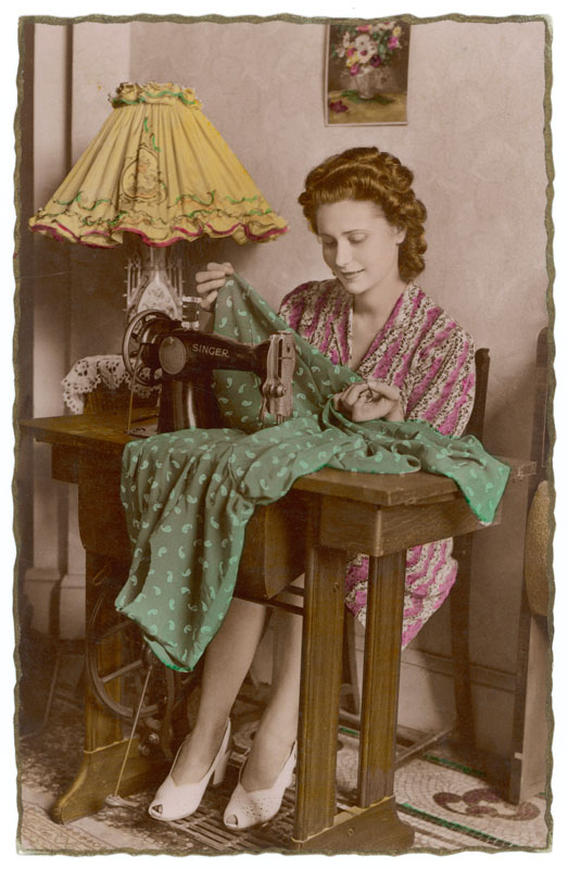 A French housewife uses the treadle to provide power for her Singer sewing machine.   1940s