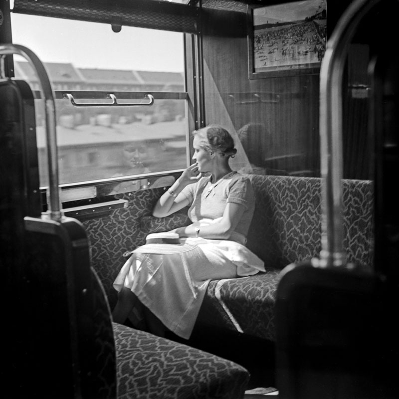 Woman looking out of a train window.  1930s