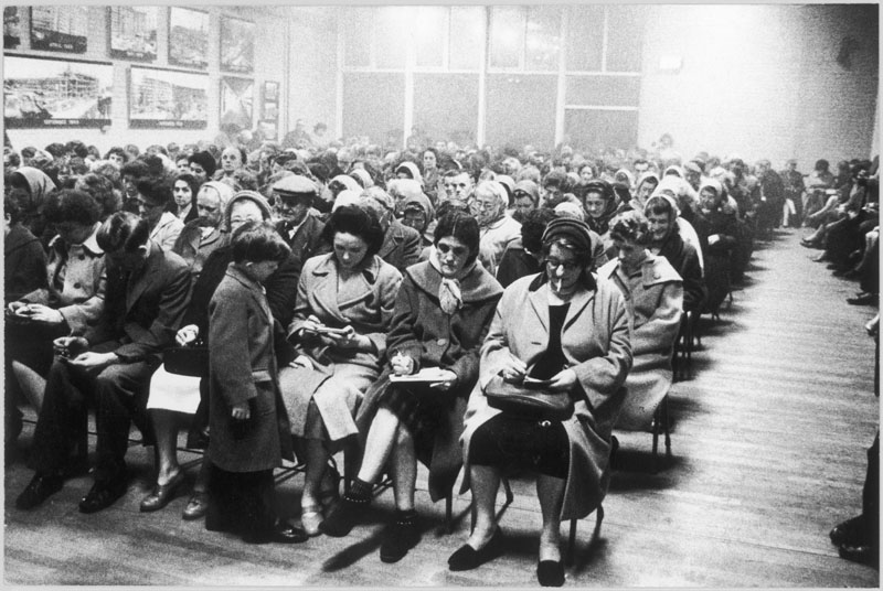 "A small boy on the front row  is intrigued by women with  ""eyes down"" for bingo on the  front row at the Old People's  Club on the Park Hill Estate,  Sheffield, Yorkshire, England.     Date: 1961"