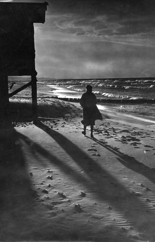A young woman walks home along  a deserted beach at dusk.         Date: 1940s