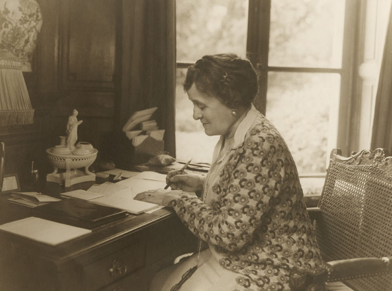 Edith Wharton, writes at her desk in 1920. She is best known for her dramatic fiction set in Gilded Age wealth, the world in which she grew up and lived in as an adult.